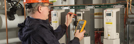 Personnel using a Fluke multimeter to control a circuit in an industrial environment